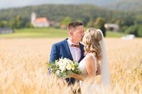 Bride and groom kissing and hugging tenderly in wheat field somewhere in Slovenian countryside.
