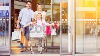 Familie mit Kindern im Einkaufswagen beim Shopping