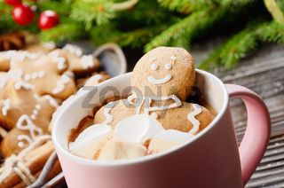 Pink mug with hot chocolate marshmallows and gingerbread man on background of spruce branch and tray with cookies