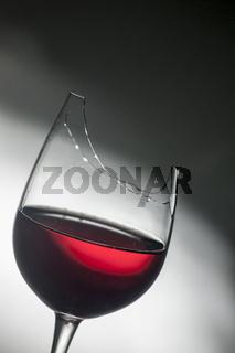Upper part of broken red wine glass
