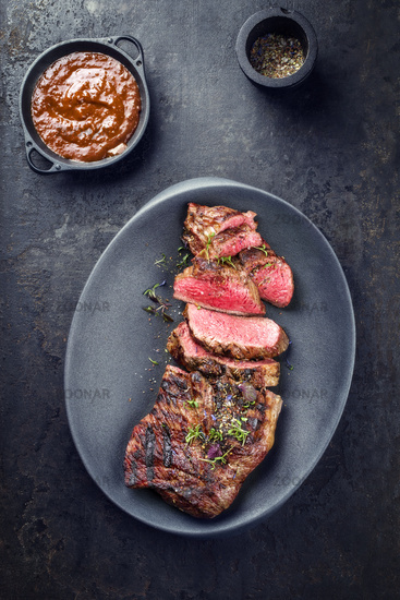 Barbecue dry aged wagyu tri tip steak sliced with hot sauce as top view in a modern design cast iron plate