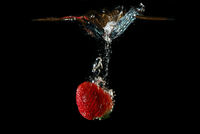 fresh healthy strawberry falls quickly in water and injected and produced bubbles with black background