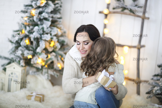 Beautiful happy mother with lher ittle daughter in knit sweater sitting on the background of Christmas interior