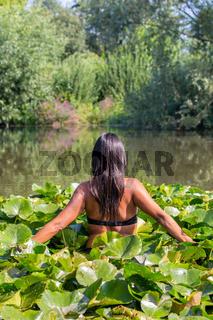 Colombian woman walking through water lilies
