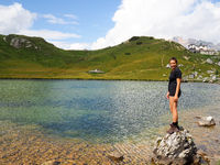 attractive brunette in her twenties standing on a boulder in a mountain lake