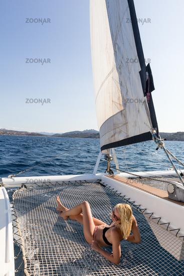 Beautiful woman relaxing on a summer sailing cruise, lying and sunbathing in hammock of luxury catamaran sailing around Maddalena Archipelago, Sardinia, Italy in warm afternoon light