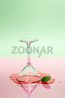 Glass martini glass and spilled liquid on a pink-green background. Modern art photography.