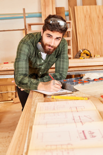 Junger Handwerker mit einer Bauzeichnung