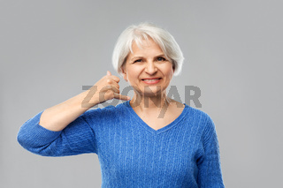 smiling senior woman making phone calling gesture