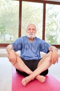 Senior Mann sitzt entspannt auf eine Yoga Matte