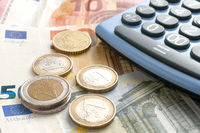 Some euro coins on euro banknotes and a calculator