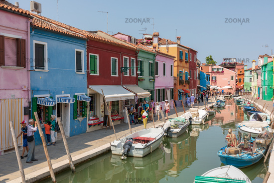 Panoramic view of coloured homes and water canal with boats in Burano