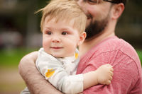 Close-up portrait of adorable baby smiling with his hipster father.