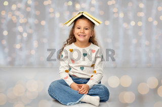 portrait of smiling girl with book on head