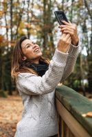 Portrait of Happy woman making selfie in the autumn park full of yellow leaves.