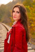 A gorgeous young woman with long brown hair and red leather jacket in fall scenery outdoors, with railroad tracks on background. Fashion concept portrait in autumn natural light, close-up shot