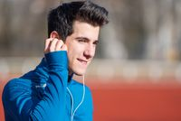 Handsome Sportive young Man Runner Putting On Earphones.