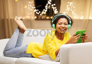 woman with tablet pc and earphones on christmas