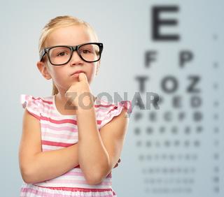 little girl in glasses over eye test chart