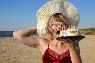 girl eats cake on the beach in a hat.