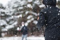 Young Happy friends enjoying throwing Snow balls, Having Fun in a Snowy Mountain.