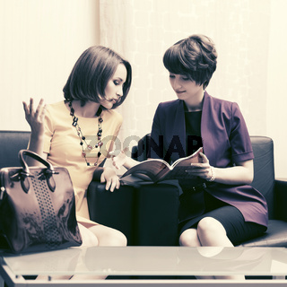 Two young fashion business women sitting on couch in showroom