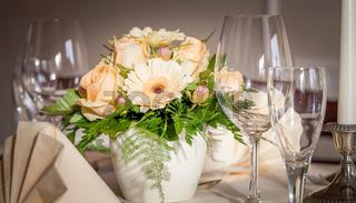 Festliches Tisch-Arrangement mit Gläser und Servierten und Blumen