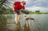 senior male launching racing kayak