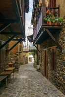 Ancient village Kakopetria in Cyprus - travel architecture background. Stunning view of the street in old town. Pots with flowers standing on paved pavement along stone wall