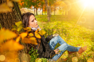 Beautiful romantic girl with perfect skin and complexion, in a park autumn scenery, sitting down and leaning against a tree, enjoying the perfect weather in a sunny day. Gorgeous young woman outdoors
