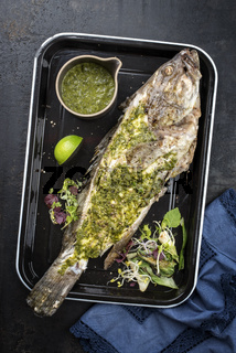 Barbecue white grouper with chimichurri sauce aji criollo as top view in a black skillet