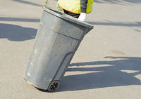 A cleaner carries a dumpster down the street.Regular garbage collection.Focus on a dumster.
