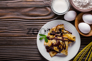 Flat lay French crepes with chocolate sauce walnuts eggs and flour on wooden kitchen table