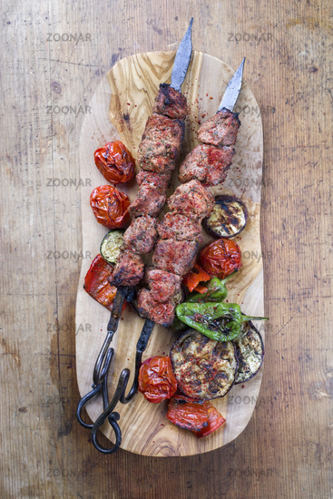 Traditional Russian shashlik on a barbecue skewer with vegetable and sumach as top view on a wooden cutting board with copy space
