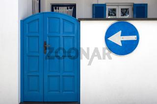 Eingangstür aus Holz in Blau mit Verkehrsschild nach links