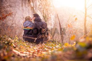 Loving couple enjoys the mountain view, beautiful scenery with sundown, autumn