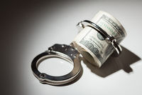 Handcuffs Locked on Roll of One Hundred Dollar Bills Under Spotlight