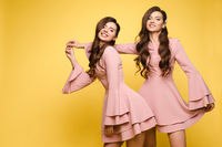 Happy sisters in pink dresses smiling and standing together.
