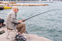 old man fishing on a fishing rod in the sea, in the evening