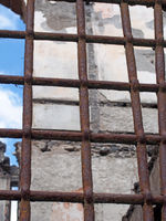 close up of a rusting iron fence with bars in front of a ruined collapsing building