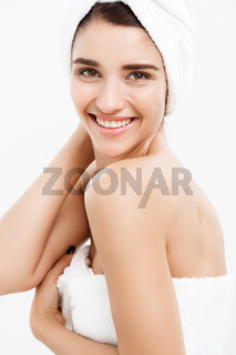 Beauty and Skin care concept - Beautiful caucasian Young Woman with bath towel on head covering her breasts, on white touching her skin.