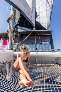 Woman relaxing on a summer sailing cruise, sitting on a luxury catamaran near picture perfect Palau town, Sardinia, Italy.