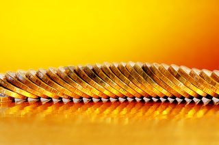 Coins lying on the Golden surface with a Golden background