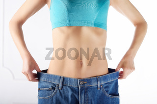 Caucasian female model in blue jeans showing her flat stomach. Weightloss concept.