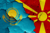 flags of Kazakhstan and North Macedonia painted on cracked wall