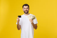 Young handsome happy smiling man holding banking card and cash in his hands isolated on yellow background.