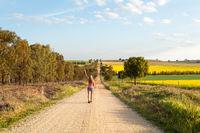 Woman walking along a dusty road among the rural fields