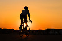 silhouette of young man riding racing bicycle with sunset sky background