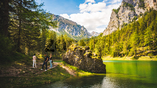 Gruner See, Austria 16.05.2017: Peaceful mountain view with famous green lake in Styria. Turquoise green color of water. Tourists walking on the shore. Travel destination