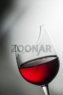 Upper part of broken wine glass with red wine